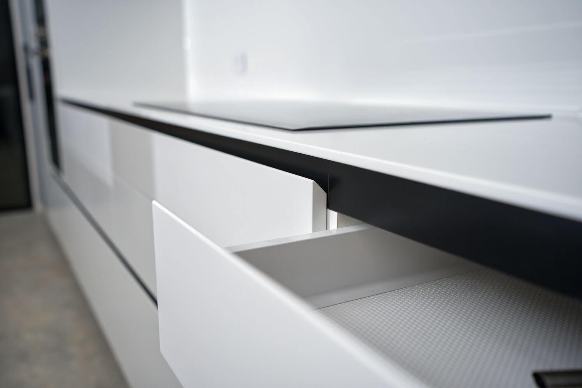White custom designed kitchen draws with shaped edge in place of handles